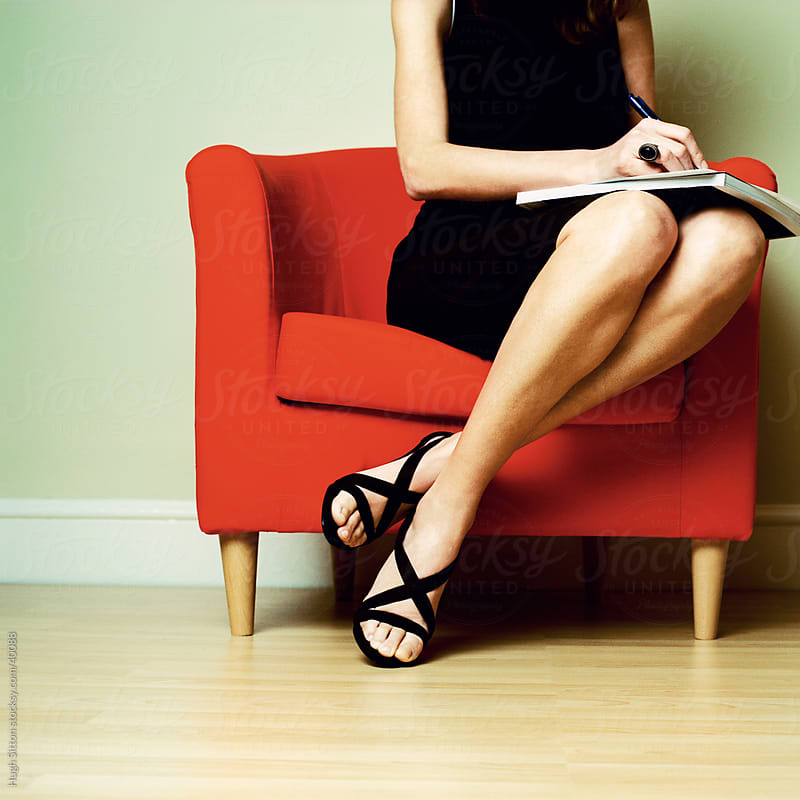 Businesswoman writing in notebook. by Hugh Sitton for Stocksy United