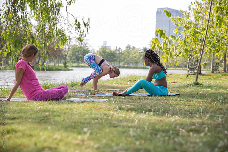 Yoga in a park - three girlfriends exercising together  by Jovo Jovanovic for Stocksy United