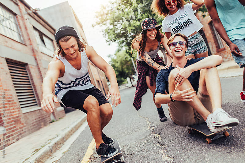 Young friends with skateboards having fun on the city street by Jacob Lund for Stocksy United