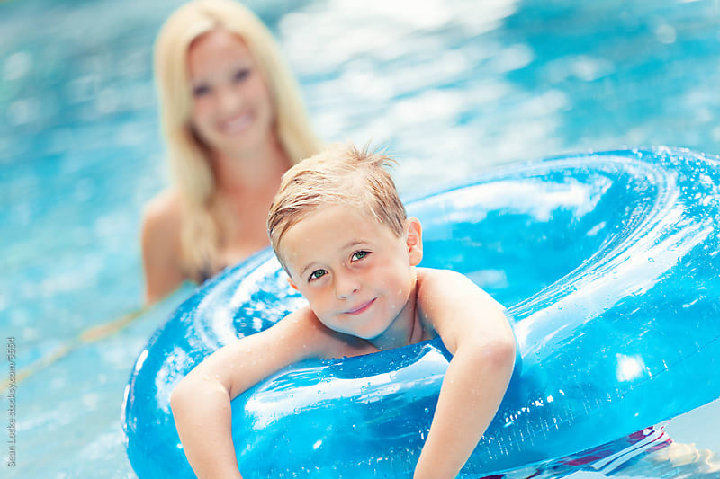 Swimming: Young Boy in Inflatible Tube With Mother by Sean Locke for Stocksy United
