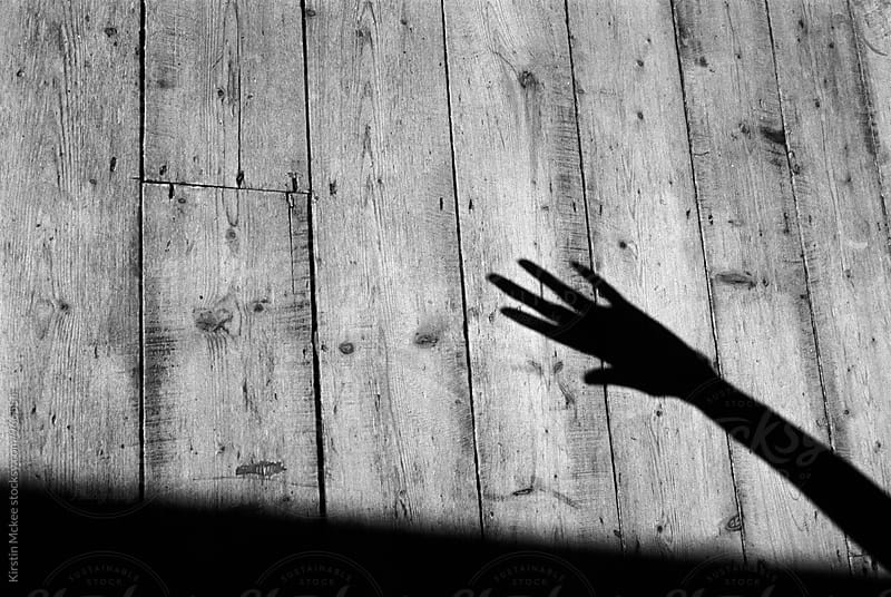 Shadow of hand on authentic wooden floor by Kirstin Mckee for Stocksy United
