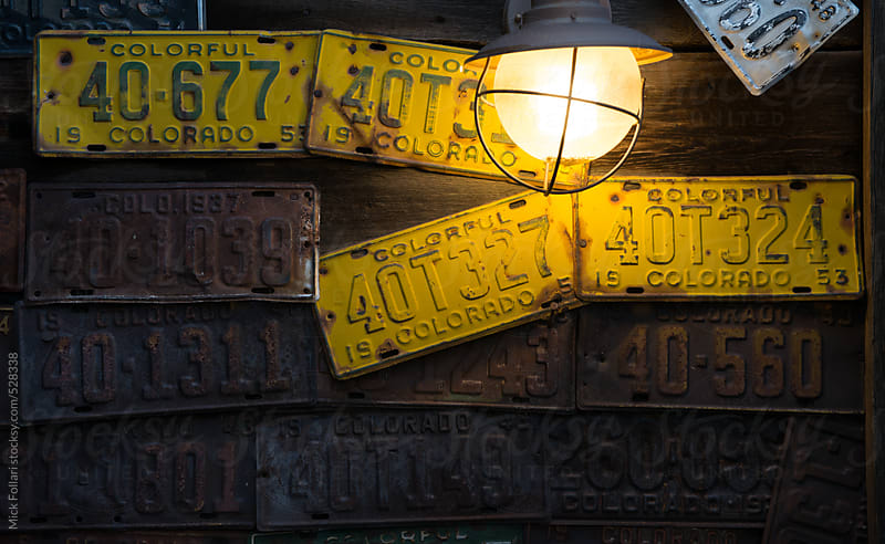 Crooked old license plates and  vintage outdoor lamp on exterior wall by Mick Follari for Stocksy United