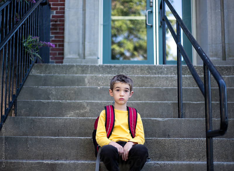 Boy sits on steps in front of school looking unimpressed by Cara Dolan for Stocksy United