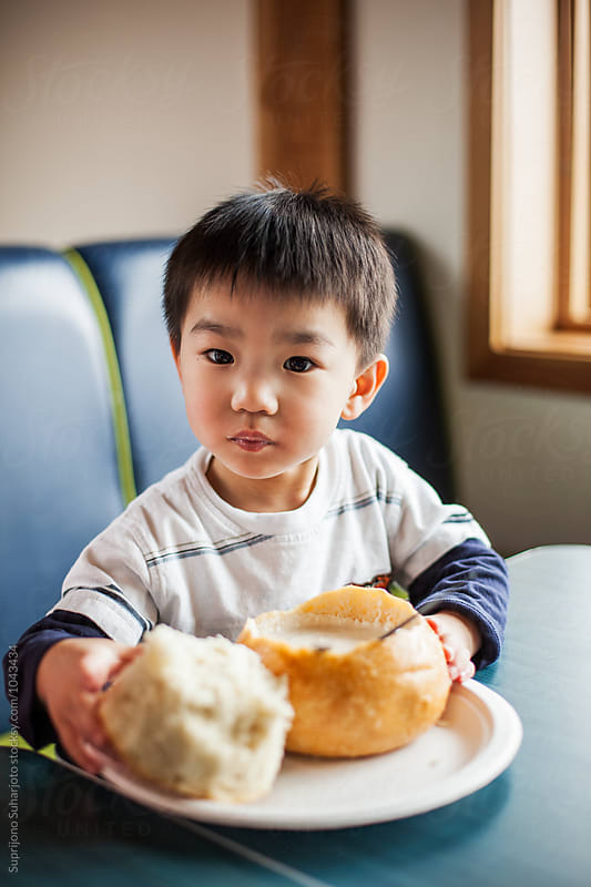 Asian boy eating clam chowder in a bread bowl by Suprijono Suharjoto for Stocksy United