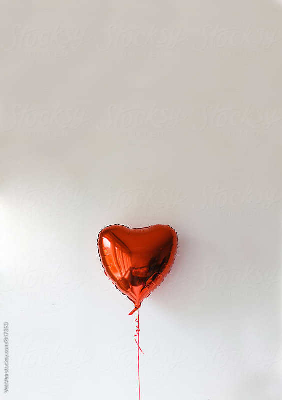 Heart shaped balloon in front of a white background  by Marija Mandic for Stocksy United