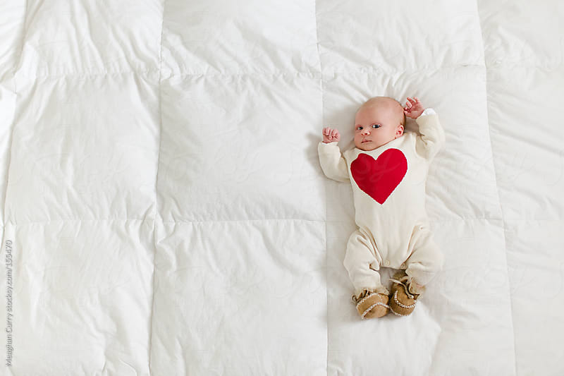 newborn in a heart onesie by Meaghan Curry for Stocksy United