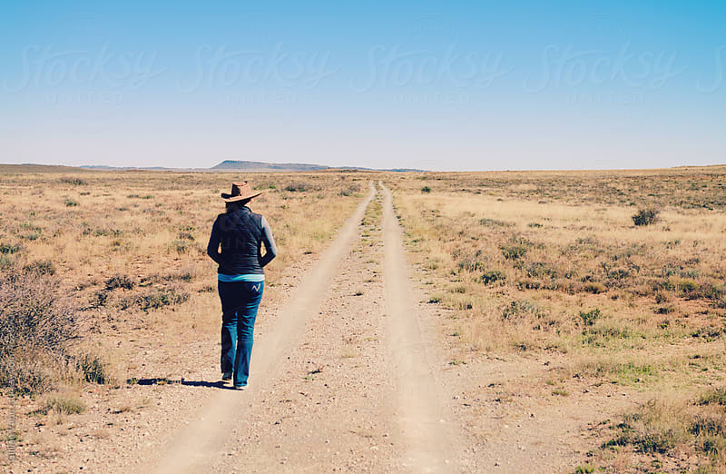 woman walking on dirt road in a flat, dry, rural scene by Gillian Vann for Stocksy United