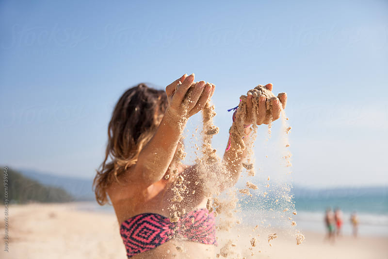 Beautiful woman in bikini playing with sand by Jovo Jovanovic for Stocksy United
