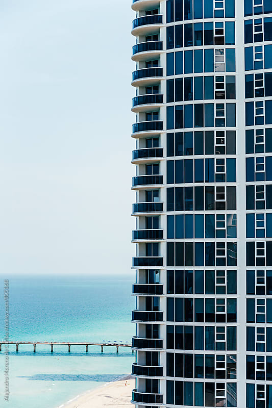 Tall block of modern apartments skyscraper with views of a beach and turquoise water by Alejandro Moreno de Carlos for Stocksy United