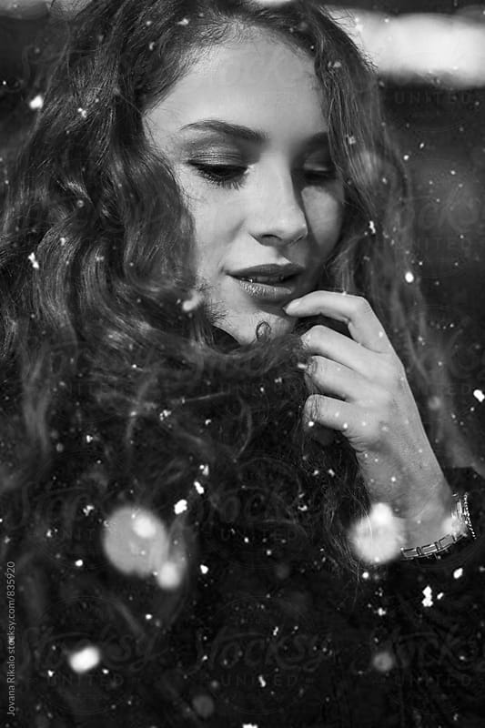 Black and white photo of a young woman and a snow by Jovana Rikalo for Stocksy United