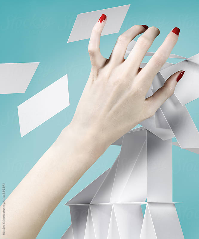 hand reaching a tower of cards by Naoko Kakuta for Stocksy United