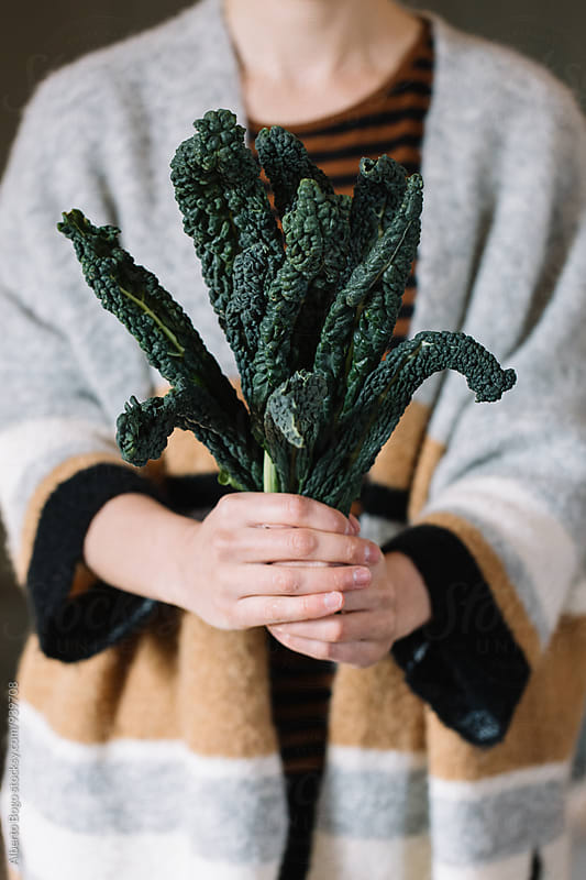 Woman holding black cabbage by Alberto Bogo for Stocksy United