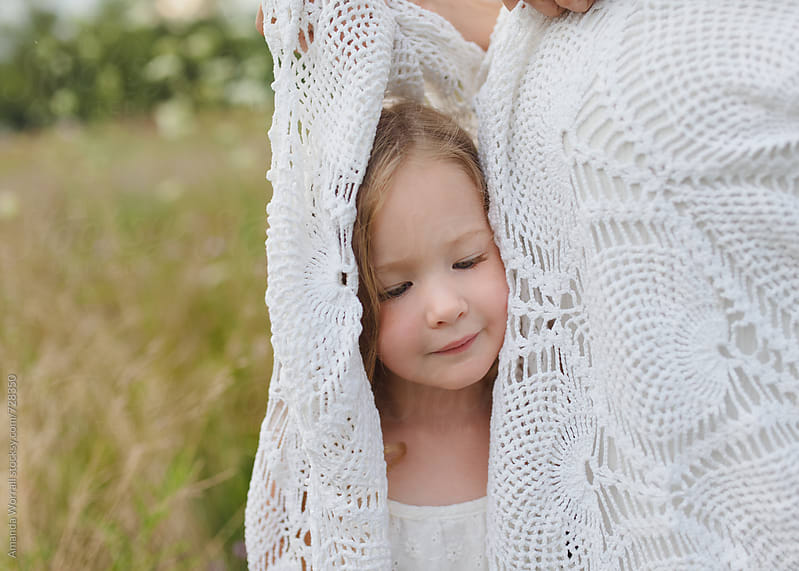 Beautiful 3 year old covered by a white lace blanket by Amanda Worrall for Stocksy United