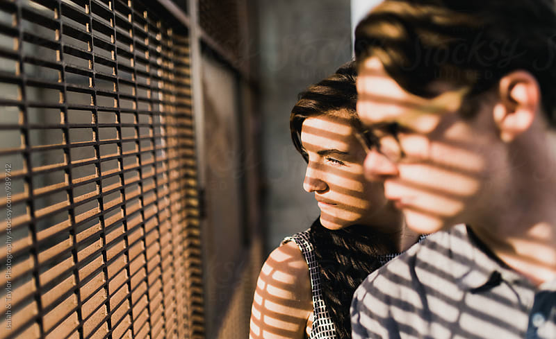 Two young adults looking out toward sun by Isaiah & Taylor Photography for Stocksy United