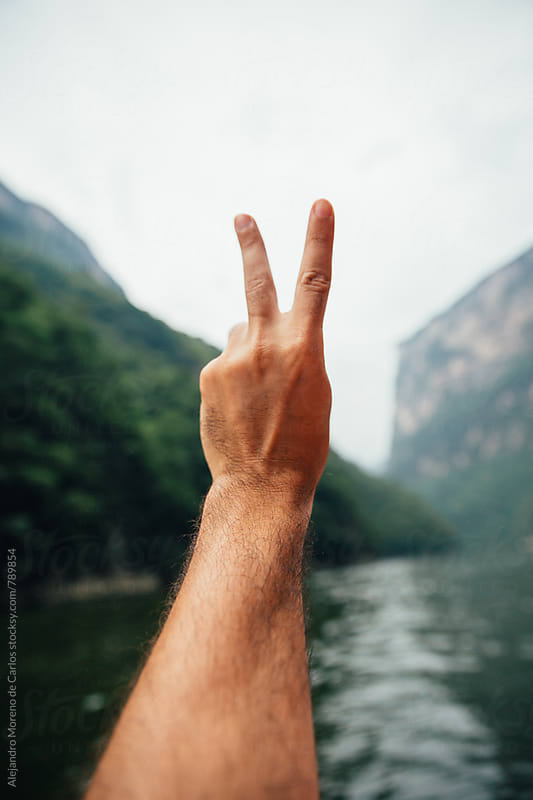 Close up of a male hand making the victory sign with a scenic view of canyon and lake in Chiapas, Mexico. POV view by Alejandro Moreno de Carlos for Stocksy United