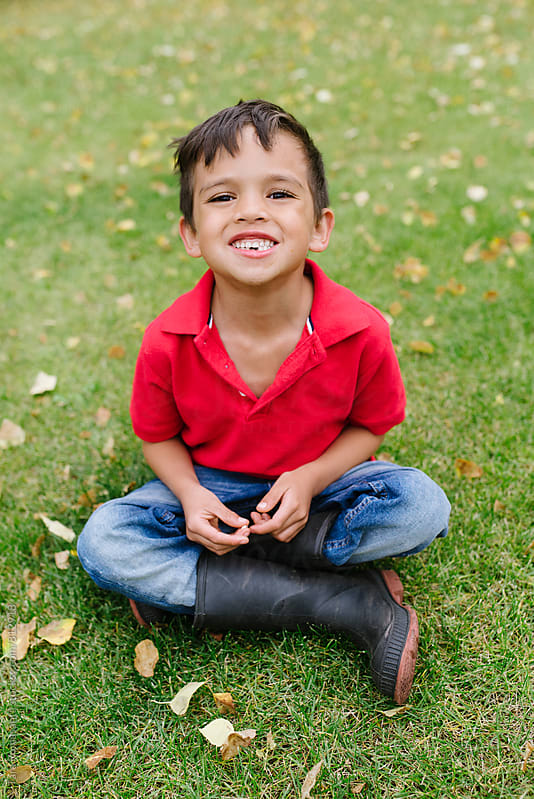 child grinning with lost teeth by Tara Romasanta for Stocksy United