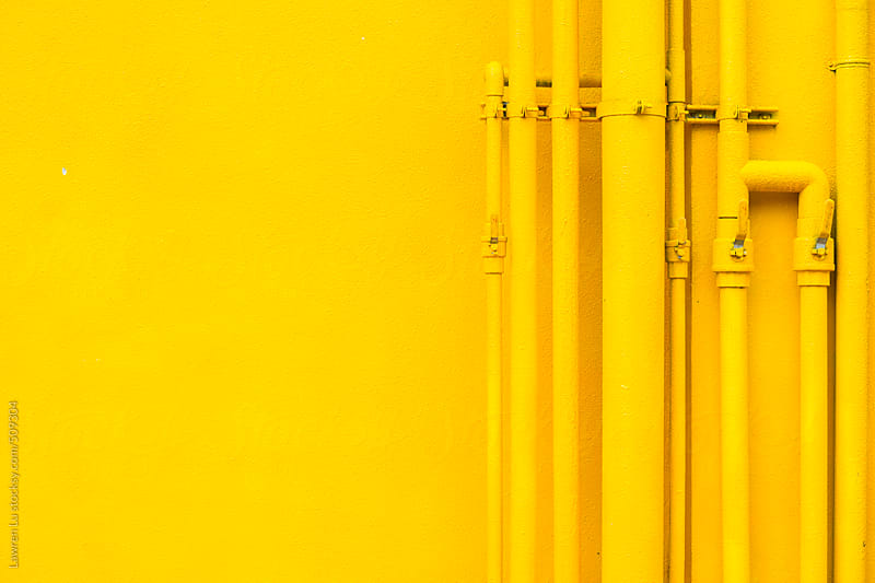 Many yellow pipes arranging in line on yellow wall by Lawren Lu for Stocksy United