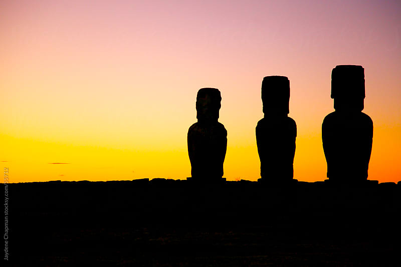 An orange sunrise coming up behind three Moai stone statues, Easter Island, Chile by Jaydene Chapman for Stocksy United