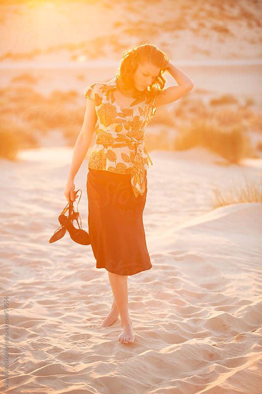Woman walking on the sand id desert at sunset by Aleksandra Kovac for Stocksy United