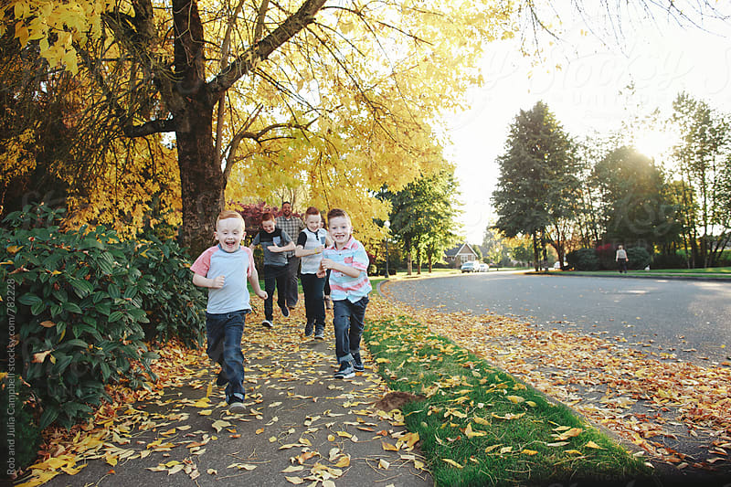 Young family having fun together in fall with yellow leaves by Rob and Julia Campbell for Stocksy United