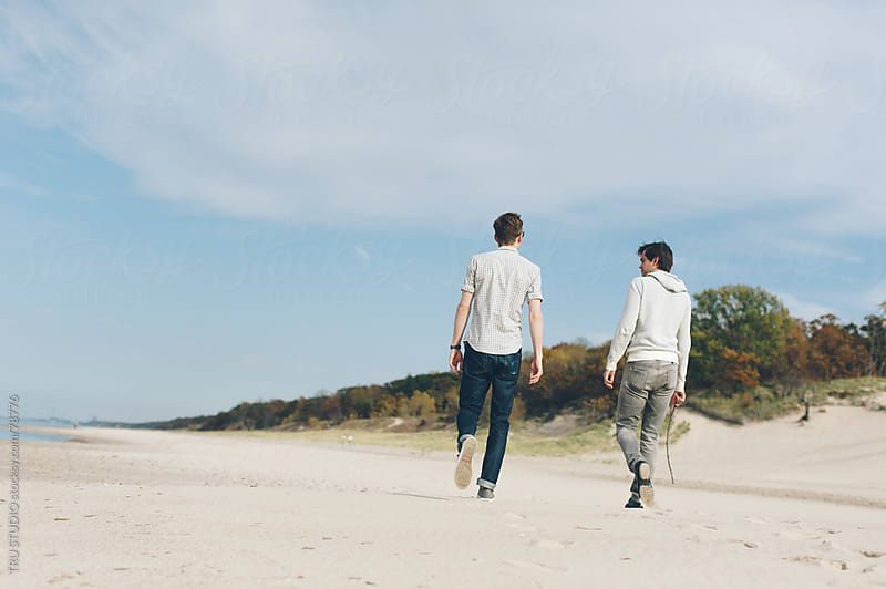 Young men walking on beach on sunny day with sand dunes. by TRU STUDIO for Stocksy United