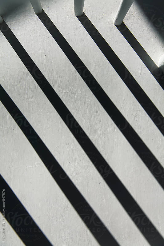 Afternoon window light casting a long shadow on white chair.  by RZ CREATIVE for Stocksy United