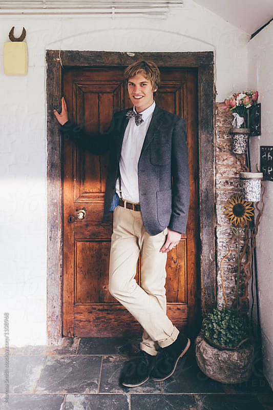 A real groom standing in the doorway  of a farmhouse on the day of his wedding