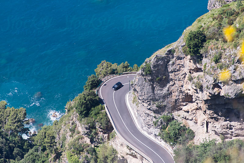 A winding road on cliff next to the ocean with a car coming around the corner by Mike Marlowe for Stocksy United
