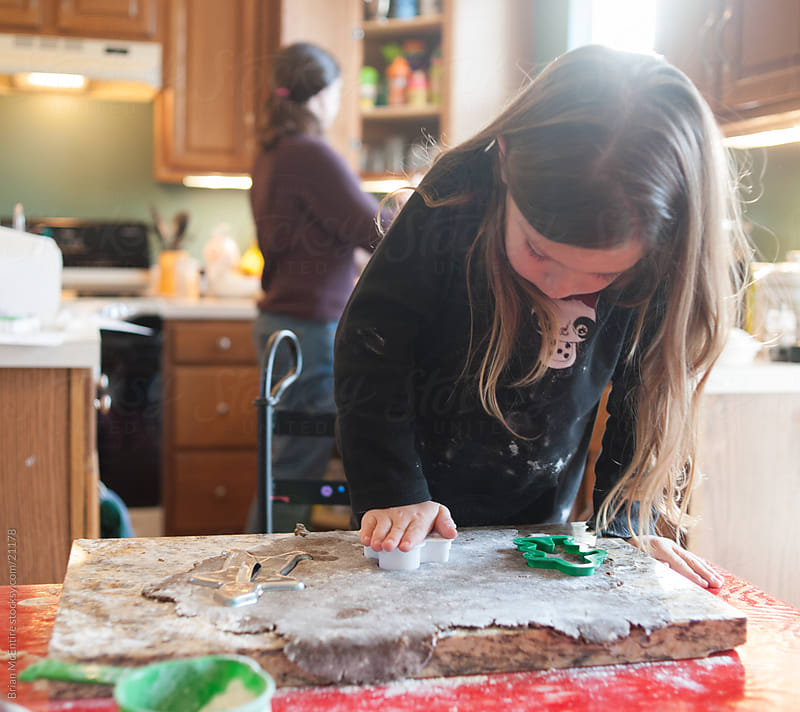 Child Baking: Daughter Helps Mother Bake Christmas Cookies by Brian McEntire for Stocksy United