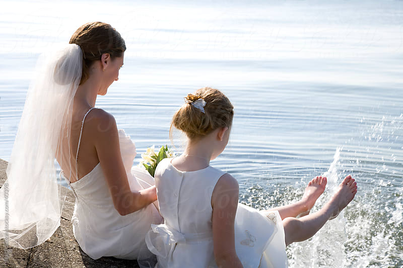 Bride and Flower Girl having fun by the sea. by Hugh Sitton for Stocksy United