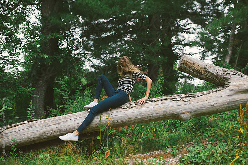 Young woman climbing a tree by Douglas Robichaud for Stocksy United