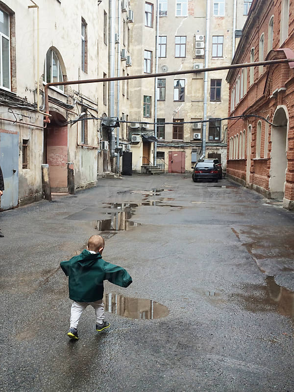 Boy running to a puddle by Lyuba Burakova for Stocksy United