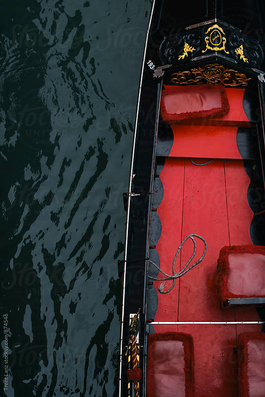 Close-up of Venitian gondola boat painted with red and black colors by Trent Lanz for Stocksy United