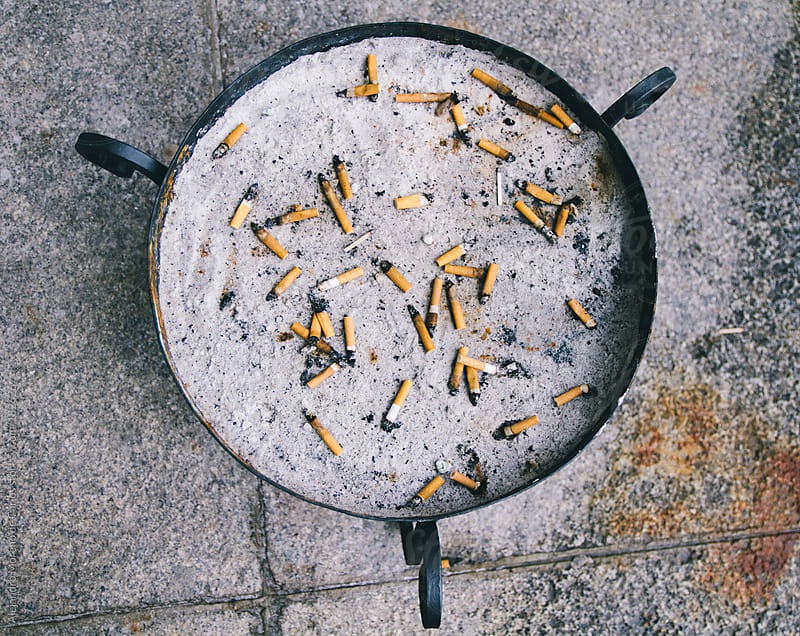 Circular metal ashtray with sand and cigarettes by Alejandro Moreno de Carlos for Stocksy United