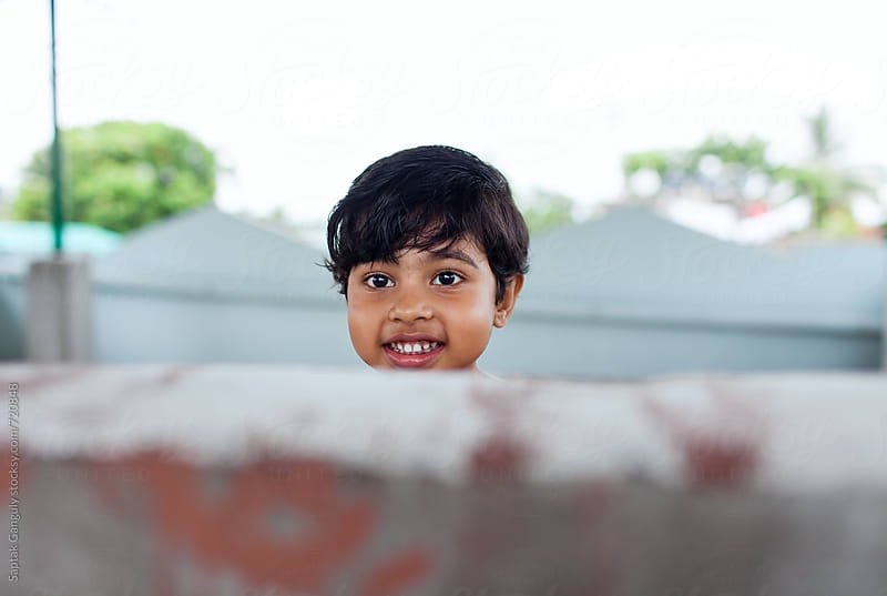 Cute little girl peeking from behind the wall and smiling by Saptak Ganguly for Stocksy United