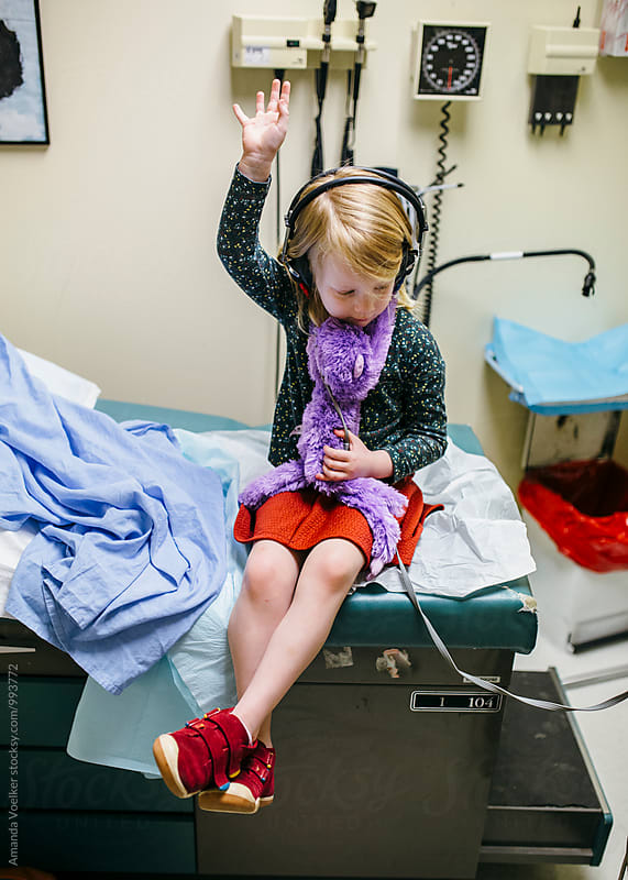 A Little Girl Raises her hand during a Hearing Test by Amanda Voelker for Stocksy United