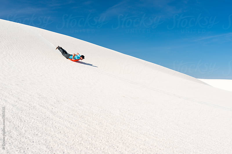 Man Sand Sledding on Sand Dune In White Sands National Monument New Mexico by JP Danko for Stocksy United