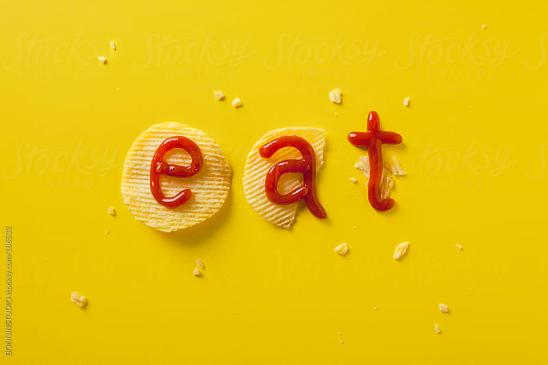 The eat word concept with potato chip and ketchup on yellow background. by BONNINSTUDIO for Stocksy United