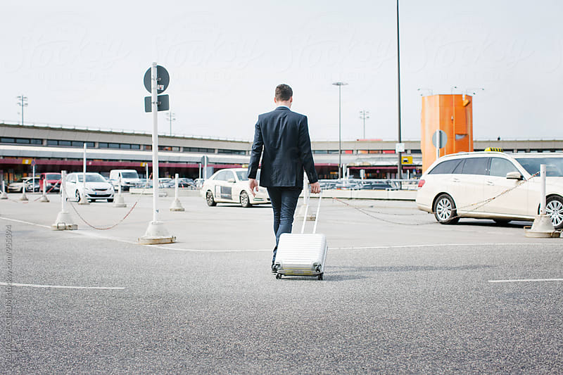 Caucasian Businessman in Suit Walking on Airport Carpark by Julien L. Balmer for Stocksy United
