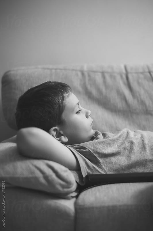 Young boy lying on a sofa in a relaxed manner with a serious face by Lea Csontos for Stocksy United