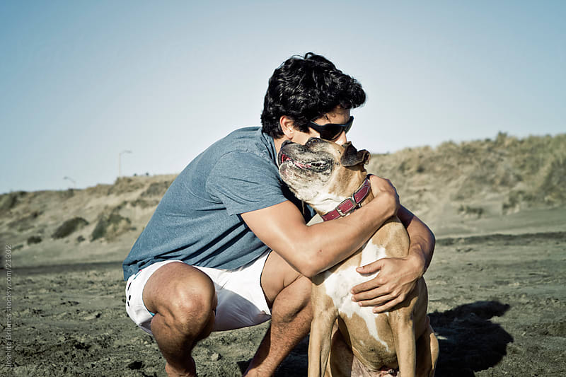 Man Hugging his Pet Boxer Dog with Affection by Joselito Briones for Stocksy United