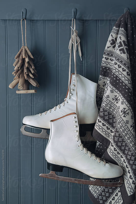 Ice skates with blanket and Christmas tee ornament on hooks by Sandra Cunningham for Stocksy United