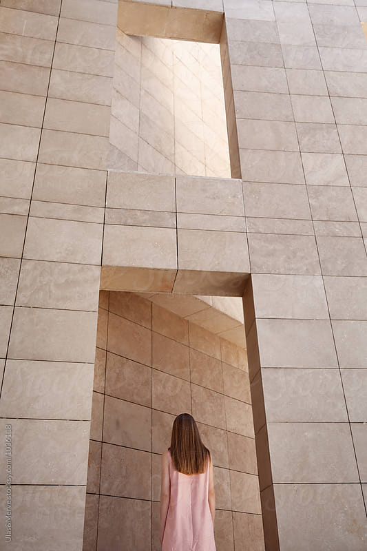 back portrait of a young blond woman with marble walls by Ulaş and Merve for Stocksy United