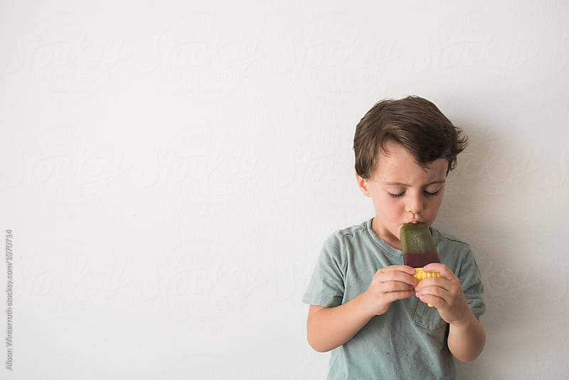 Boy Eating A Green Popsicle by Alison Winterroth for Stocksy United