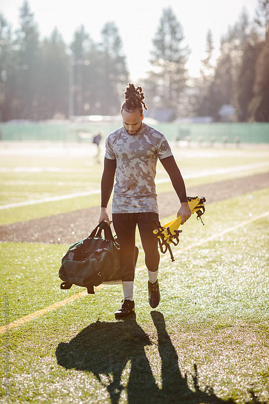 African American athlete carrying a gym bag on the football field by Suprijono Suharjoto for Stocksy United