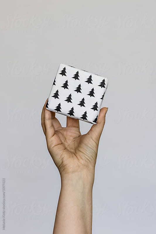 Hand holds a single giftbox by Melanie Kintz for Stocksy United