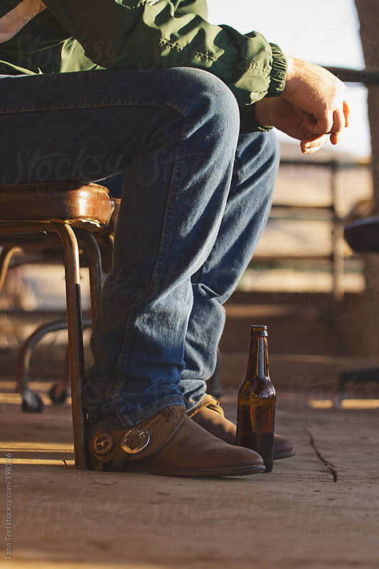 Cowboy sitting on a porch with a beer by Tana Teel for Stocksy United