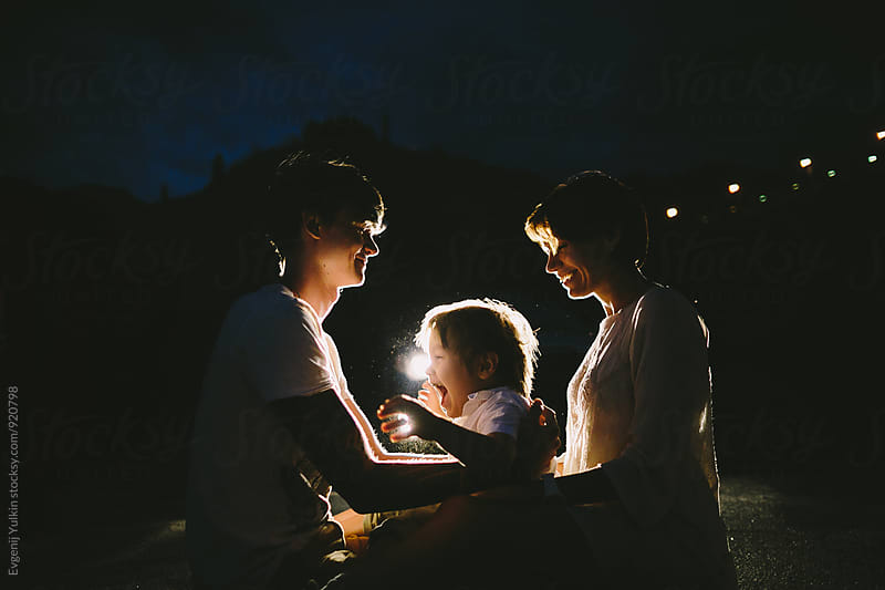 Family playing in the headlights sitting on the ground by Evgenij Yulkin for Stocksy United