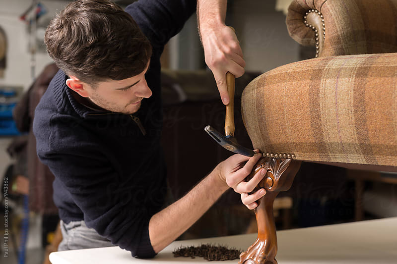 Close-up of a craftsman attaching brass studs to a re-upholstred antique chair. by Paul Phillips for Stocksy United