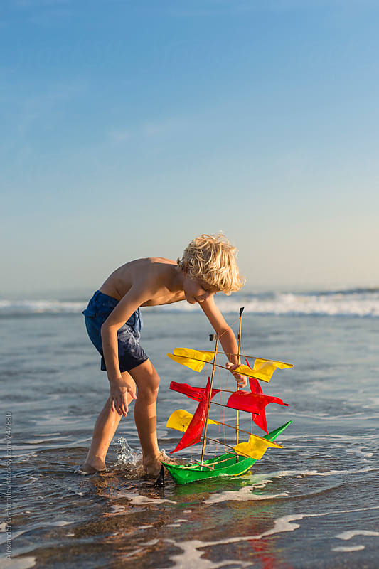 Boy playing with toy boat in sea by Alexander Grabchilev for Stocksy United